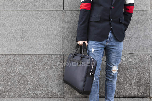 Close-up of stylish businessman standing in front of grey wall holding a bag — Stockfoto