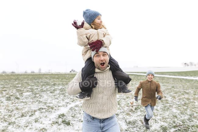 Щасливий батько з двома дітьми в зимовому ландшафті. — стокове фото