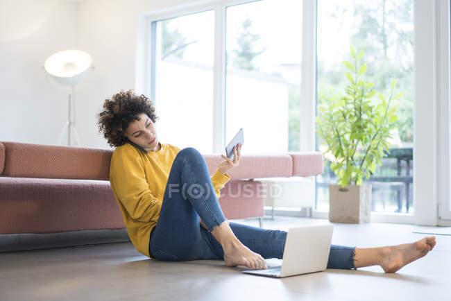 Donna che utilizza laptop, cellulare e tablet a casa — Foto stock