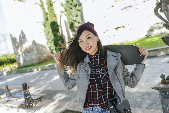 Портрет усміхнена молода жінка з скейтбордом на плечі — стокове фото