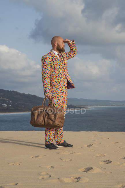 Испания, Фауста, мужчина с сумкой в костюме с мохнатыми точками польки, стоящий на дюне, глядя на расстояние — стоковое фото