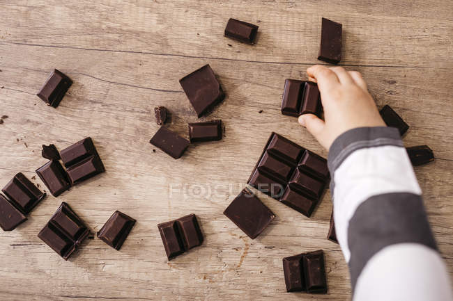 Boy's hand taking piece of chocolate — стоковое фото