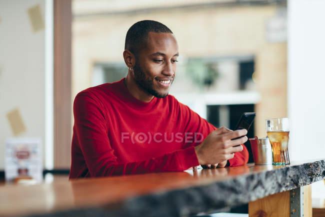 Улыбающийся молодой человек в красном свитере на стойке бара с безалкогольным напитком и мобильным телефоном — стоковое фото