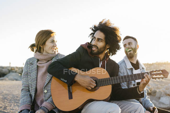 Three happy friends with guitar sitting outdoors at sunset — Stock Photo