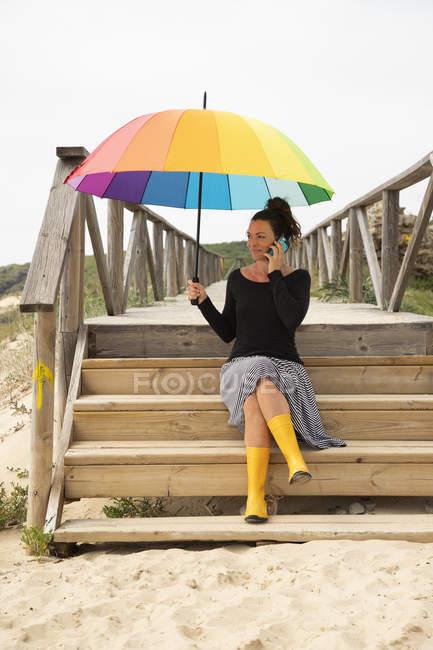 Femme avec parasol coloré debout sur la plage — Photo de stock