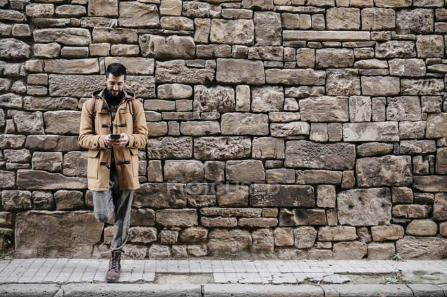 Espanha, Igualada, homem em pé na parede de pedra usando telefone celular — Fotografia de Stock