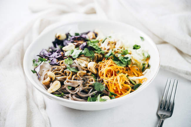 Bowl of buckwheat noodle salad with raw vegetables, roasted cashews,  coriander and spicy dressing — Stock Photo
