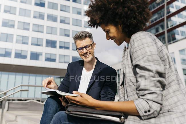 Двое счастливых коллег работают вместе за пределами офисного здания — стоковое фото