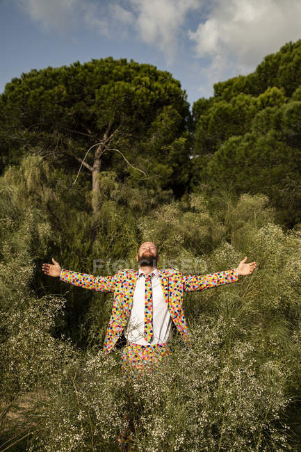 Бородатый мужчина в костюме с красочными горошинками, наслаждающийся природой — стоковое фото