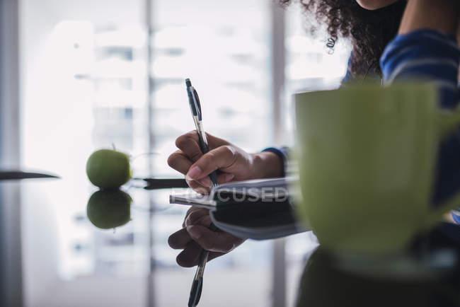 Молода жінка робить нотатки, частковий погляд. — стокове фото