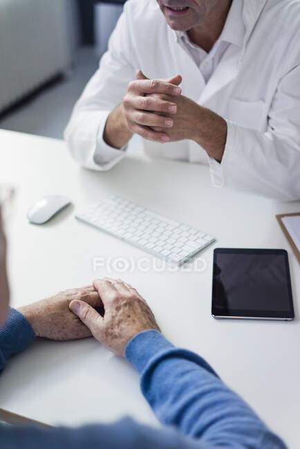 Close-up de médico conversando com paciente sênior na prática médica — Fotografia de Stock