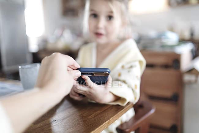 La main de la mère enlève son téléphone intelligent, gros plan — Photo de stock