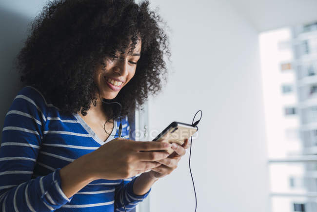 Portrait of smiling young woman with  earphones looking at cell phone — Stock Photo