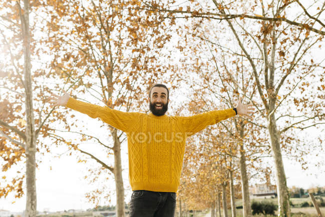 Young man with open arms and happy in a park in autumn — Stock Photo