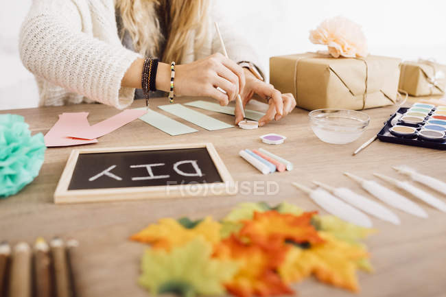 Junge Frau bastelt in ihrem Atelier mit Aquarell — Stockfoto