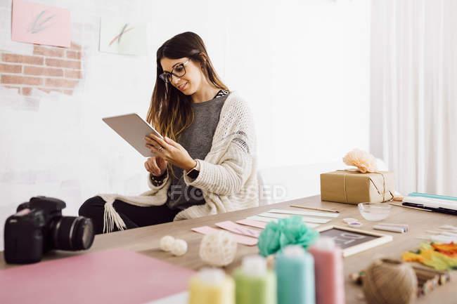 Junge Frau bastelt zu Hause, sitzt am Schreibtisch mit Tablet — Stockfoto
