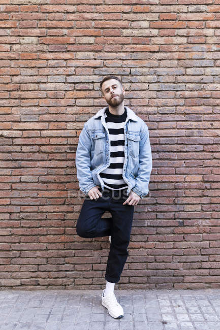 Portrait of a cool man standing at a brick wall — Stock Photo