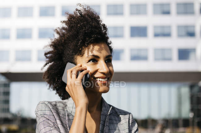Portrait of smiling businesswoman on cell phone outside office building — Stock Photo