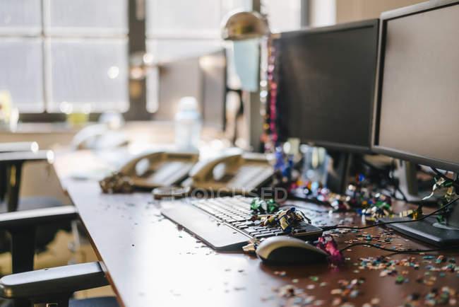 Mesa com confetti e flutores no computador após uma festa de anos — Fotografia de Stock
