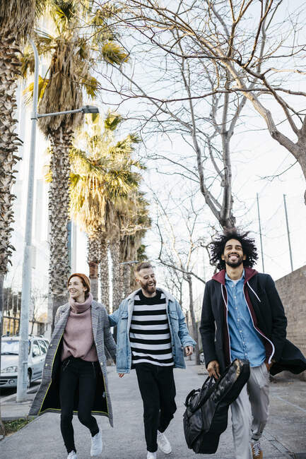 Three happy friends walking in the city — Stock Photo