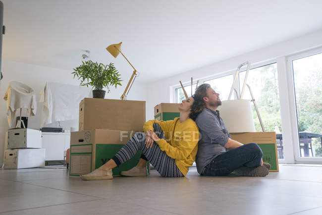 Couple sitting in living room with cardboard boxes — Stock Photo