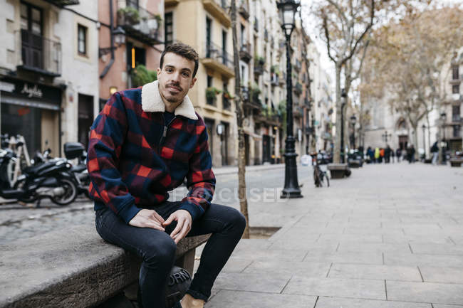Young man wearing casual clothes sitting on a bench in the city — Photo de stock
