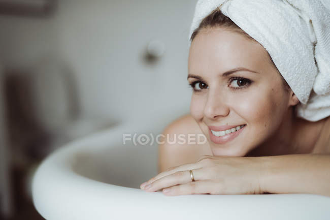 Portrait of smiling woman with towel around her head taking a bath at home — Stock Photo