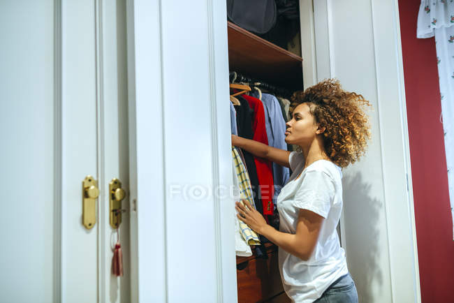 Young woman with curly hair at home looking at clothing in her wardrobe — Stock Photo