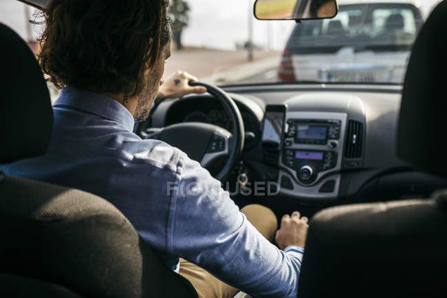 Rear view of businessman driving car — Stock Photo