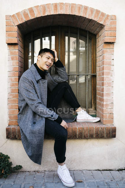 Laughing young man wearing fashionable coat sitting on window sill outdoors — Stock Photo