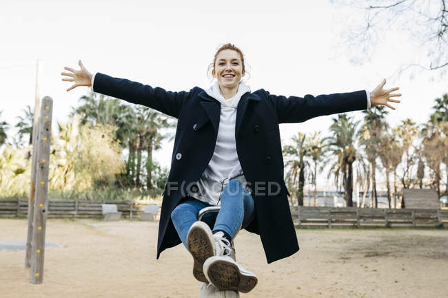 Portrait of happy young woman on a seesaw on playground — Stock Photo
