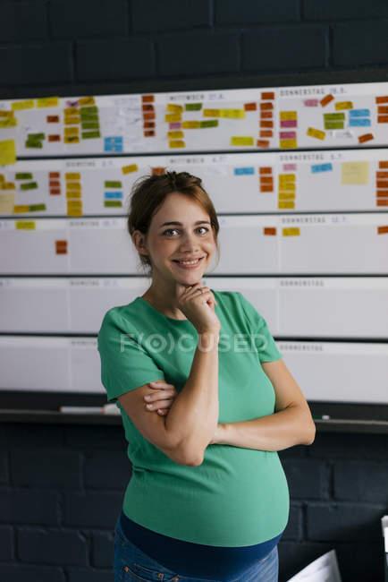 Портрет усмішки вагітної жінки, яка працює в офісі — стокове фото