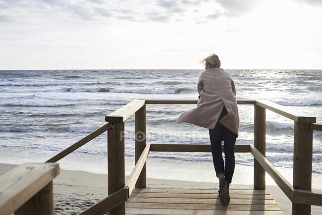 Испания, Менхенгладбах, вид сзади на пожилую женщину, стоящую на прогулке зимой и смотрящую на море — стоковое фото