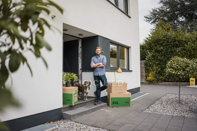 Man with dog standing at house entrance surrounded by cardboard boxes — Stock Photo