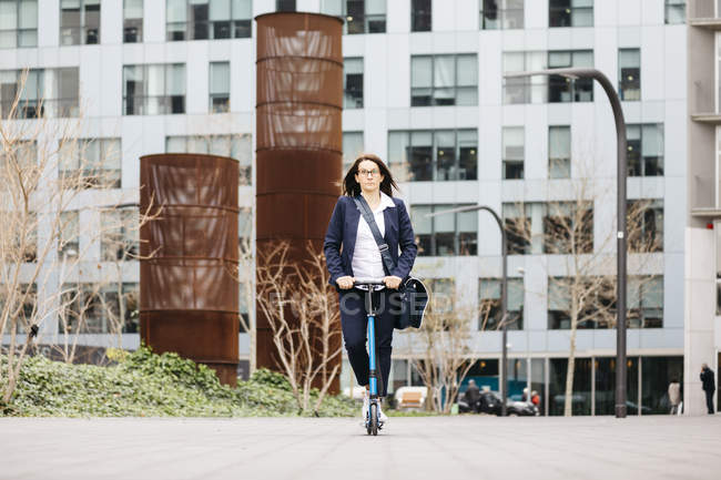Активная деловая женщина на скутере в городе — стоковое фото