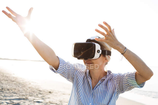Blonde woman doing kind of yoga exercises on a beach in thailand with 3D virtual reality goggles — Stock Photo