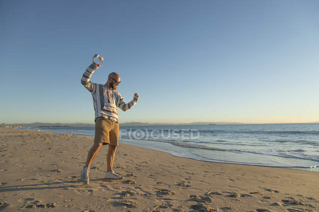 Man with headphones and sunglasses at the beach — Stock Photo