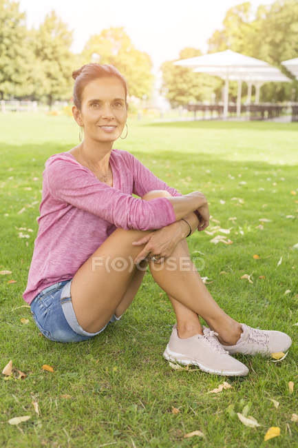Portrait of smiling mature woman sitting on a meadow in summer — Stock Photo
