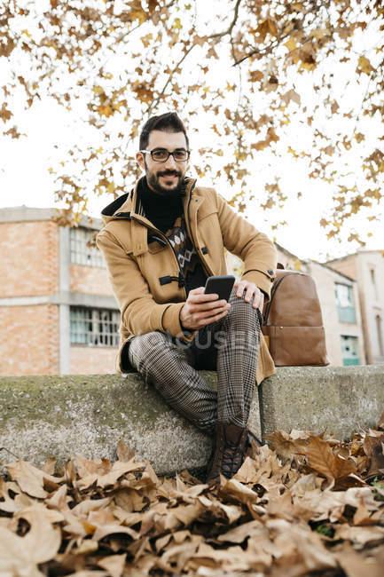 Espanha, Igualada, retrato de homem sorridente com telefone celular sentado na cidade outonal — Fotografia de Stock