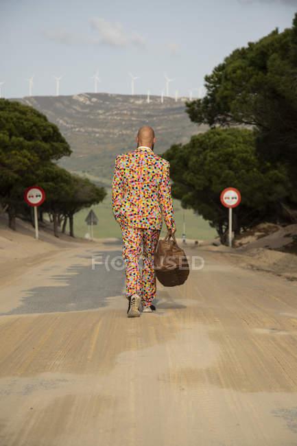 Вид сзади лысого мужчины в костюме с красочными горошинками, идущего по проселочной дороге с дорожной сумкой — стоковое фото