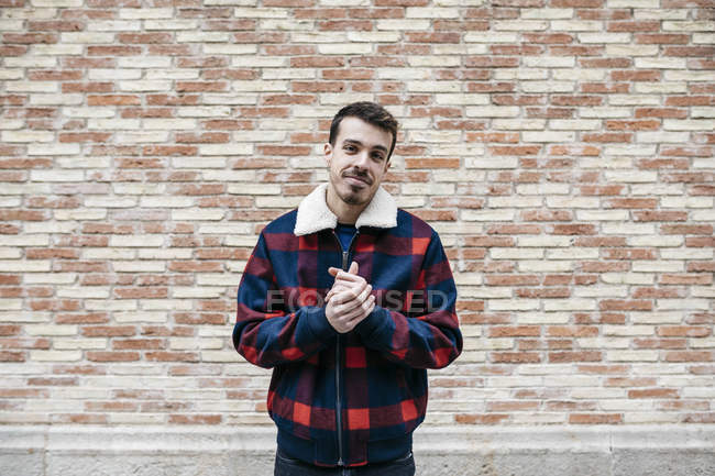 Young man wearing casual clothes rubbing his hands and looking at camera — Stock Photo