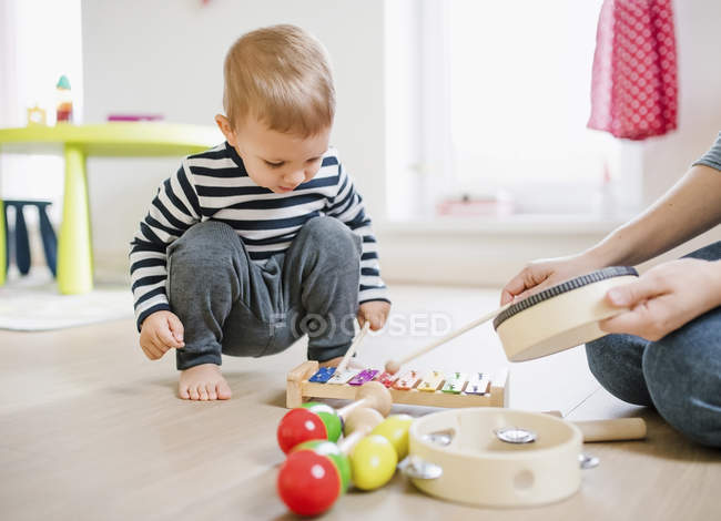 Mother and toddler son playing with musical instruments at home — Stock Photo