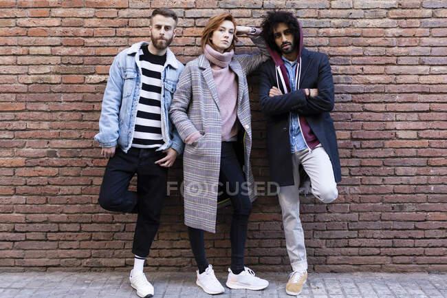 Ritratto di tre amici seri in piedi a una parete di mattoni — Foto stock