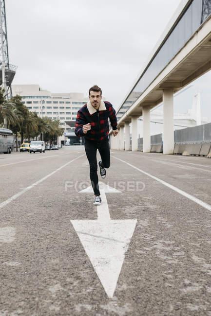 Junger Mann mit lässiger Kleidung lehnt auf dem Boden, mit einem Fuß auf einem Pfeil auf dem Boden gemalt — Stockfoto