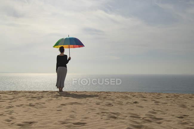 Жінка з барвистою парасолькою стоїть на пляжі. — стокове фото