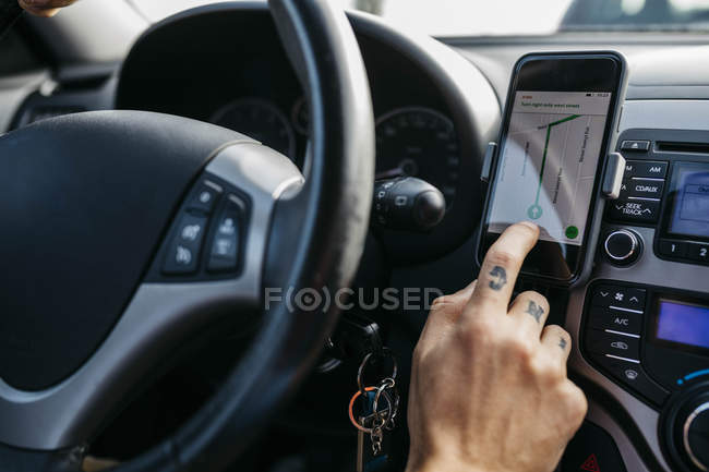 Close-up of man with tattooed hand driving car using cell phone as navigation system — Photo de stock