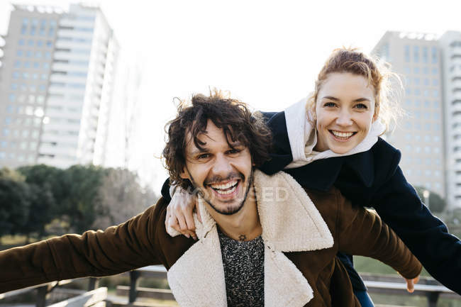 Happy couple enjoying piggyback ride in the city — Stock Photo