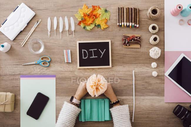 Draufsicht einer jungen Frau beim Basteln mit Papierblumen in ihrem Atelier — Stockfoto