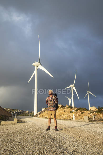 Spain, Andalusia, Tarifa, man on a hiking trip standing on dirt road with wind turbines in background — Stock Photo