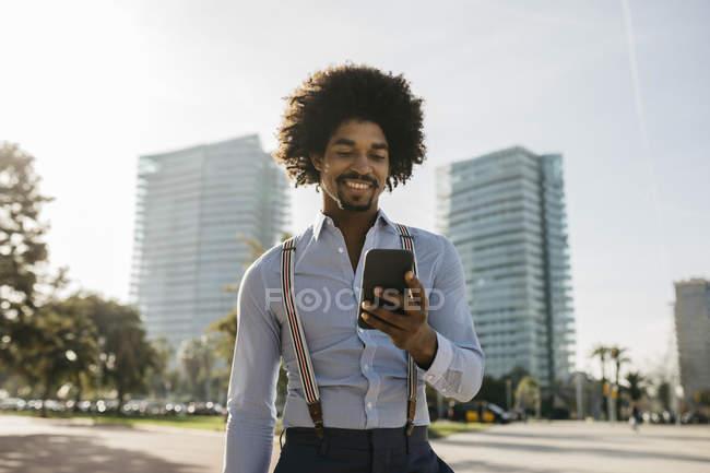 Испания, Барселона, портрет улыбающегося мужчины, смотрящего на мобильный телефон — стоковое фото